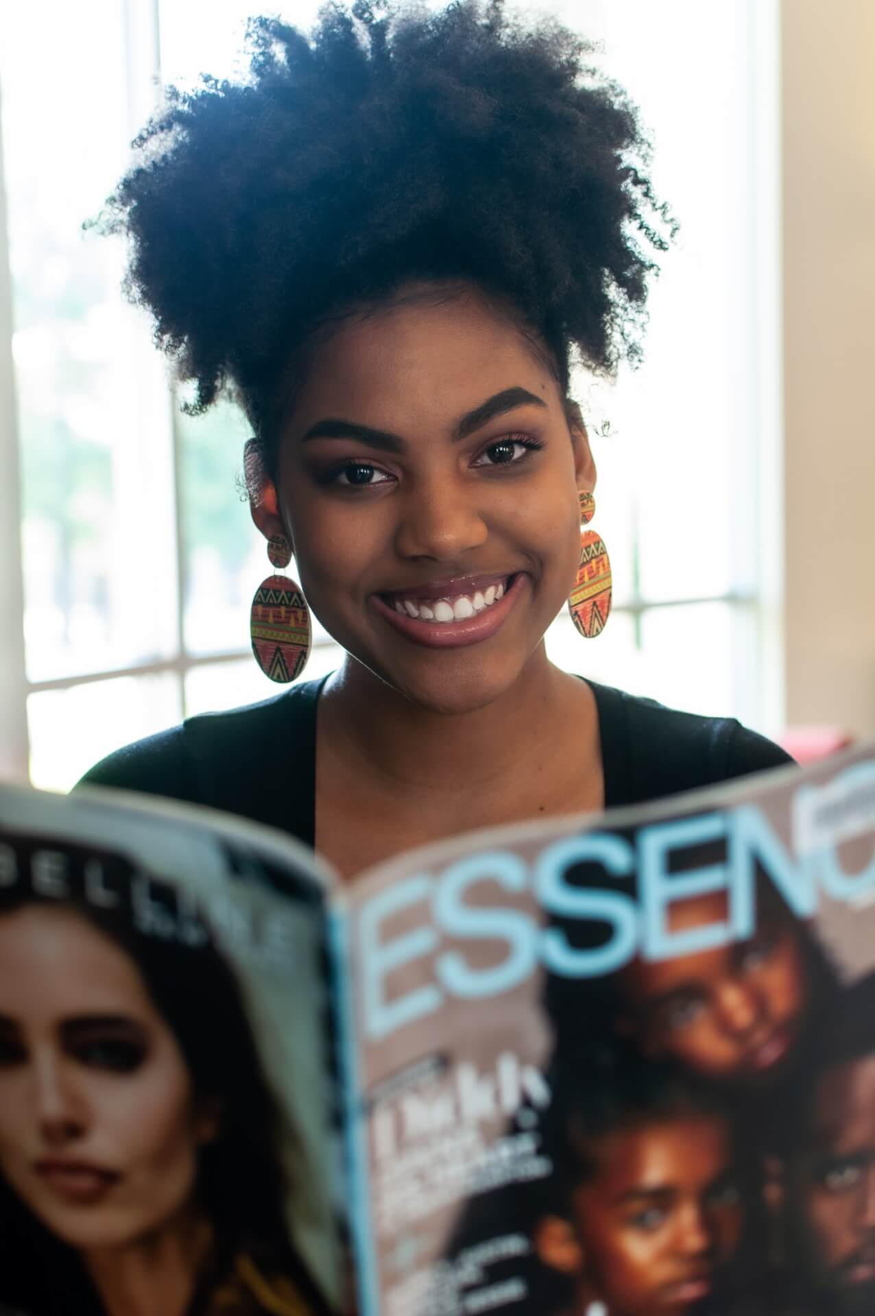 Jamee McAdoo smiling holding a copy of Essence magazine